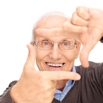 Studio shot of a senior man framing a photo with his fingers and looking at the camera isolated on white background